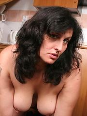 Brunette mom putting orange sex toy into hole